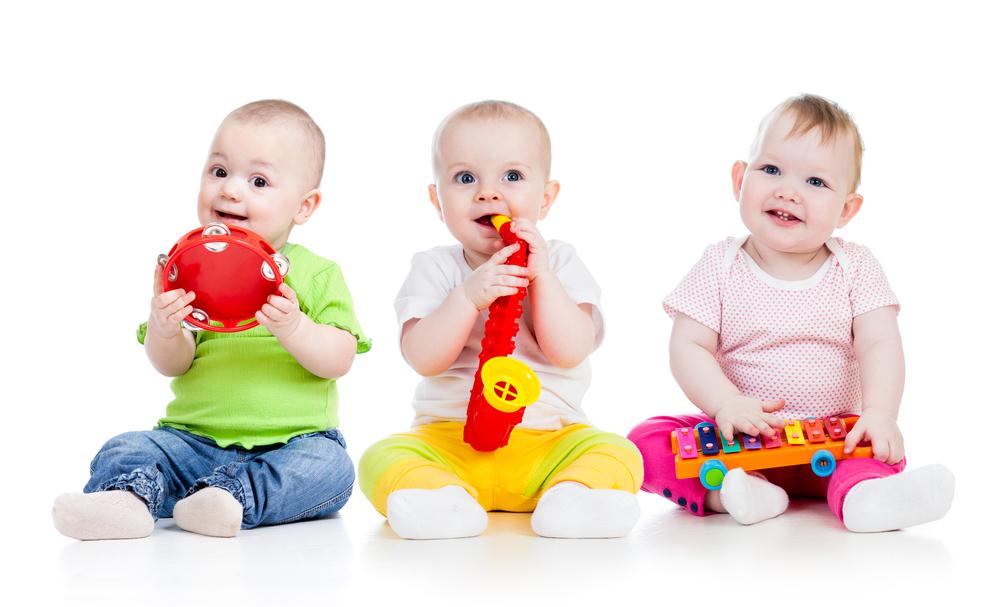 Bebés jugando con instrumetos muscales:xilófono, trompeta y pandereta