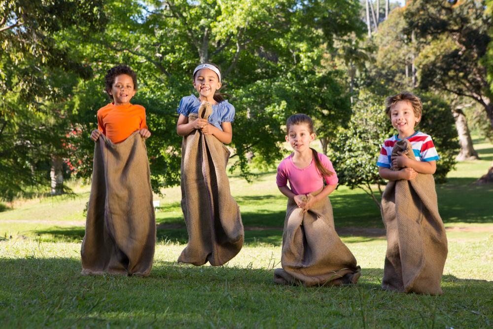 Niños jugando a la carrera de sacos en el parque