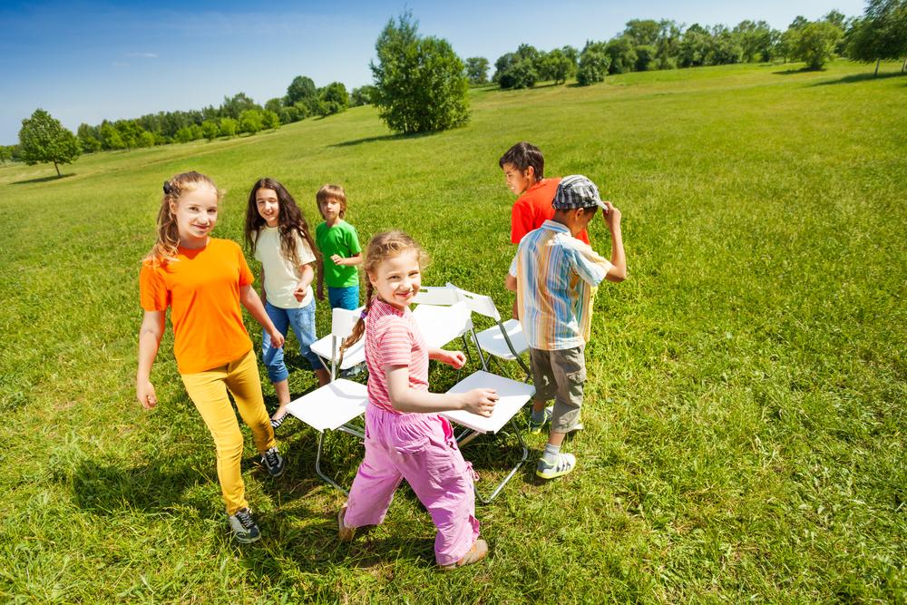 Grupo de niños jugando al juego de las sillas en un parque