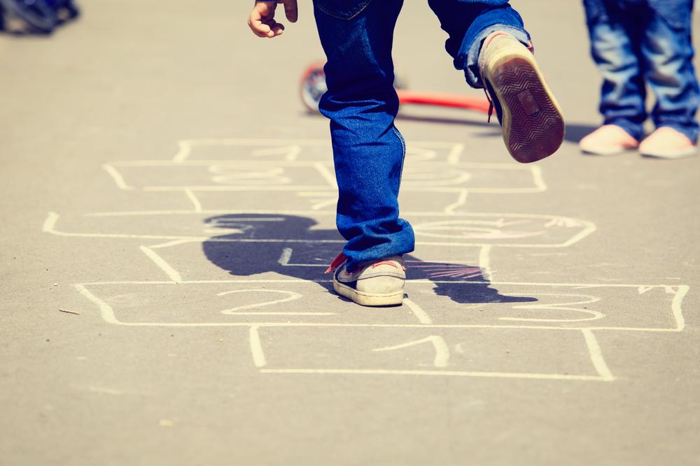 Niño jugando a la rayuela en la calle