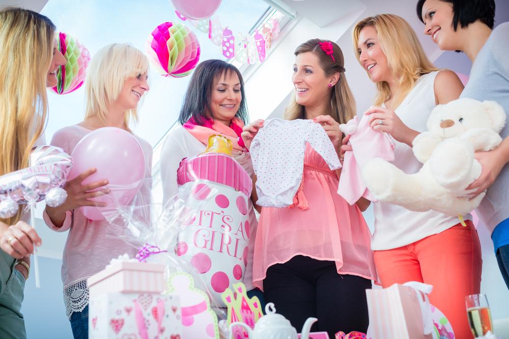 Mamá embarazada con amigas abriendo regalos en Baby Shower