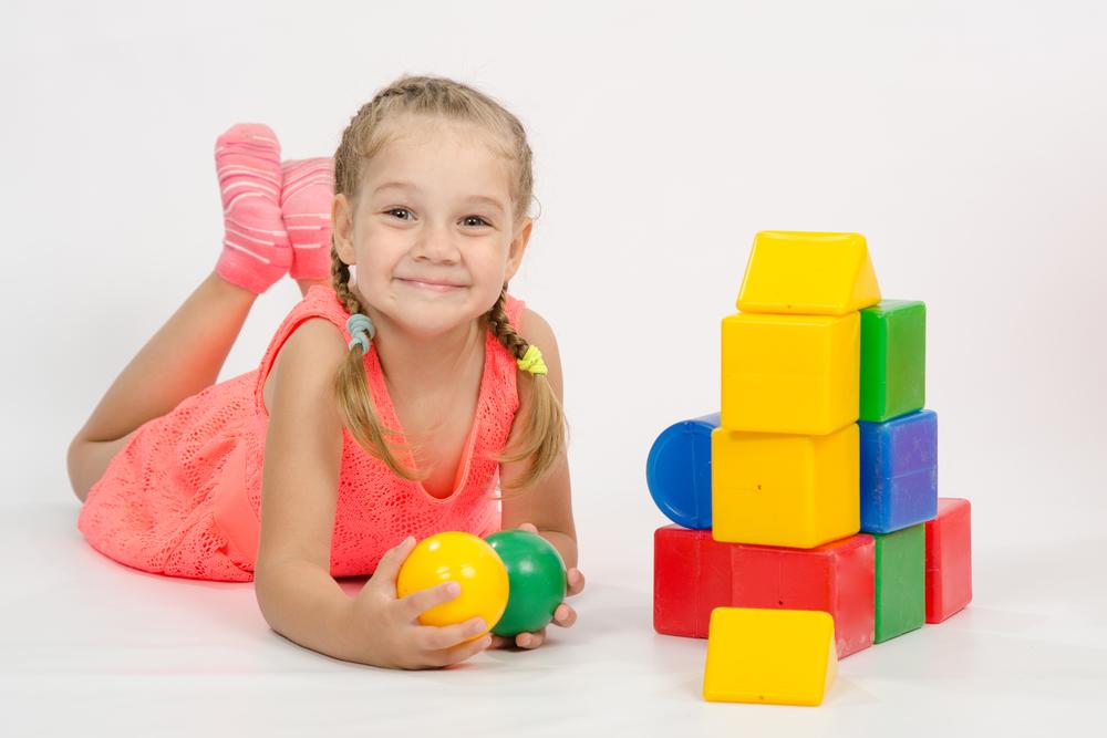 Niña en el suelo jugando con pelotas y bloques de apilar