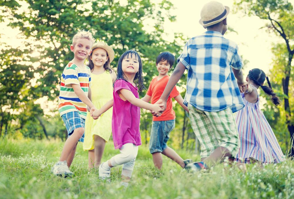 Niños jugando de la mano en círculo en un parque