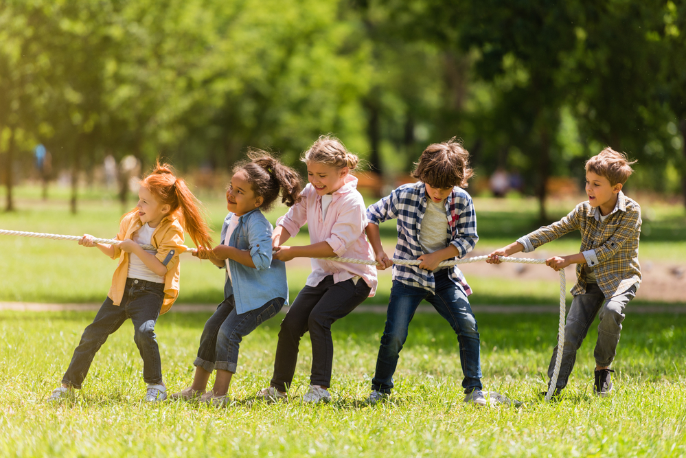 Nios jugando a tirar de la cuerda en un parque