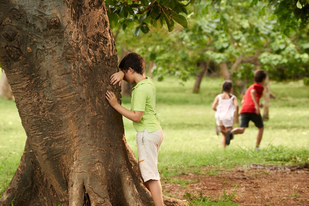 Niños jugando al escondite al aire libre. Niño apoyado en un árbol contando, los demás se esconden