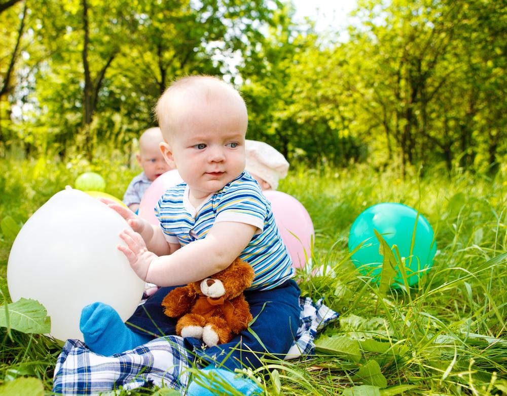 Bebés jugando en el campo con globos
