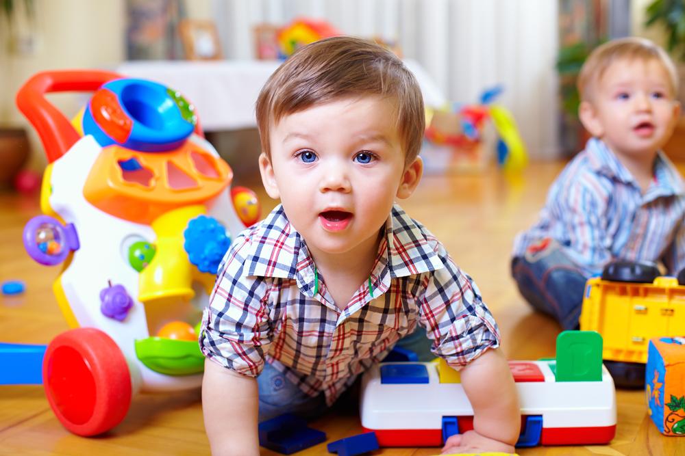 Bebés jugando en casa con juguetes de sonidos y correpasillos