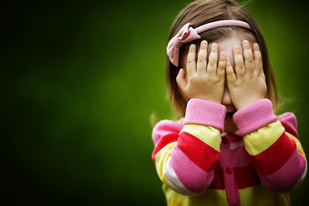 Niña con manos tapándose la cara:jugando al veo veo