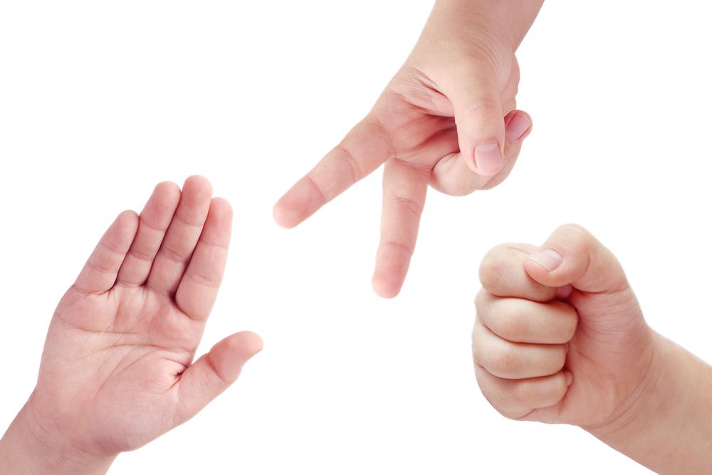 Manos de niños indicando el juego de Piedra, Papel o Tijera