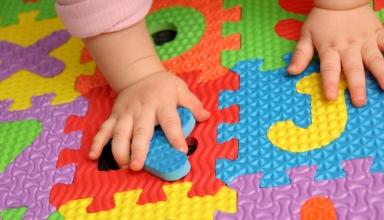 Manitas de bebé encima de puzzle de letras en el sueloletras