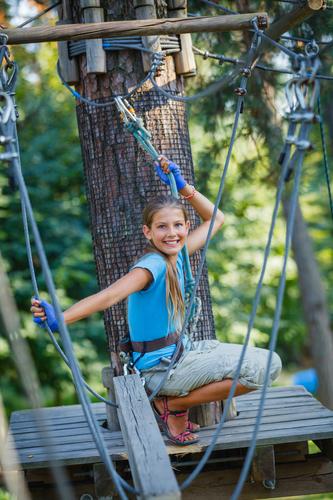 Chica en actividad de aventura en campamento