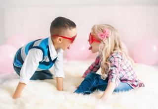 Niño y niña sacándose la lenga jugando en el suelo